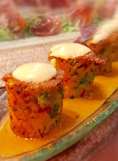 """Paella - """"sushi esque"""" bite size pieces of crispy Andalusian style paella filled with smoked chicken, peas & peppers flavored with a saffron- garlic espuma & a chorizo-tomato sauce"""
